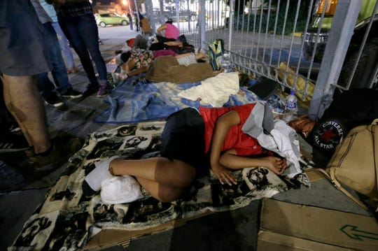 A group of Mexican migrants sleep at the base of the Paso Del Norte Bridge, where they are camping in the hope of making it to the United States.