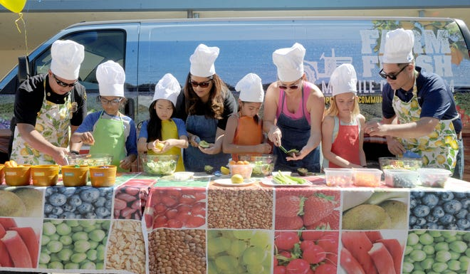 In this September 2019 photo, adult volunteers and third-graders compete in a salad-making contest as Students for Eco-Education and Agriculture's 30-foot Farm Fresh van came to Mound Elementary in Ventura.
