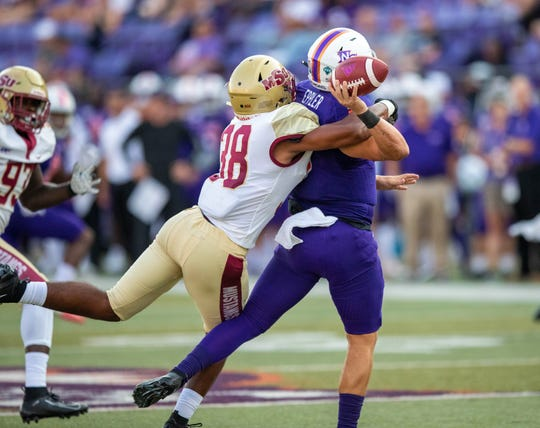 Midwestern State's Rigoberto Carrillo hits Northwestern State quarterback Shelton Eppler as he prepares to throw during the Mustangs 33-7 victory Saturday, Sept. 7, 2019, in Natchitoches, Louisiana.