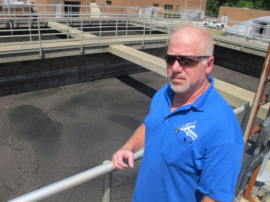In this July 31, 2019 photo, Michael Wurts, superintendent of the Lapeer Wastewater Treatment Plant, stands beside tanks of sewage sludge at the plant in Lapeer, Mich. State officials ordered Lapeer to stop distributing its sludge for use as farm fertilizer after it was found to contain toxic PFAS chemicals. Experts are raising concerns that sludge spread on agricultural fields around the U.S. could contaminate crops. About half of the 7 million tons of sludge generated each year is applied to farm fields and other lands.