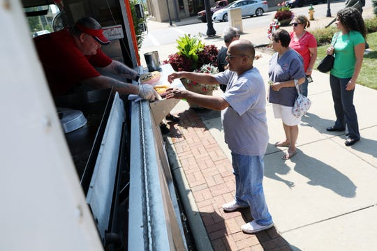 Mitchell Asher collects his lunch from Pucky's Pitstop during a food truck rally in downtown Zanesville to help kick off the United Way of Muskingum, Perry and Morgan's annual campaign on Friday.