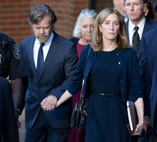 Felicity Huffman and her husband, actor William H. Macy, leave the federal courthouse in Boston after her sentencing in the college admission scandal on Sept. 13. She was sentenced to 14 days in prison, a $30,000 fine and 250 hours of community service.