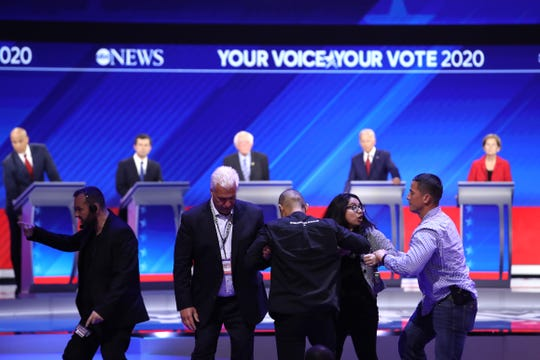 Protesters are escorted out of the auditorium by security during the Democratic Presidential Debate at Texas Southern University's Health and PE Center on Sept. 12, 2019 in Houston, Texas.