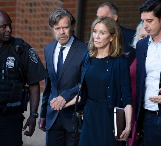 Felicity Huffman and her husband, actor William H. Macy, leave federal court in Boston after she was sentenced to 14 days in prison, a $30,000 fine and 250 hours of community service for her part in the college admission scandal, on Sept. 13, 2019.