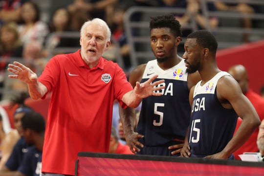 United States coach Gregg Popovich talks to Donovan Mitchell and Kemba Walker.