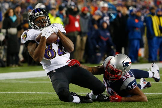 Baltimore Ravens wide receiver Torrey Smith catches a pass in front of New England Patriots cornerback Brandon Browner during 2014 AFC Divisional playoff game at Gillette Stadium.