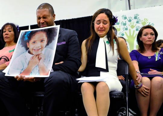 Jimmy Greene, foreground left, Nelba Marquez-Greene, center, parents of Sandy Hook Elementary School shooting victim Ana Marquez-Greene, and Nicole Hockley, right, mother of victim Dylan Hockley, react during a news conference at Edmond Town Hall in Newtown, Conn., Monday, Jan. 14, 2013. One month after the mass shooting at the school, the parents joined a grassroots initiative called Sandy Hook Promise to support solutions for a safer community.
