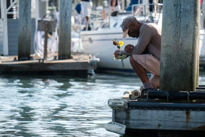 James Miranda, right, of Santa Barbara, holds flowers and takes a moment to reflect at a dock near the Sea Landing at Santa Barbara Harbor on Sept. 2, 2019. A fire raged through a boat carrying recreational scuba divers during a Labor Day weekend retreat.
