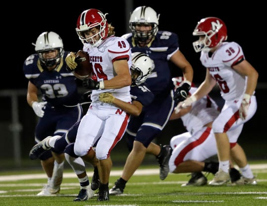 Appleton North's Sam Thao (24) tackles Neenah's Sam Jung during Friday's game in Appleton.