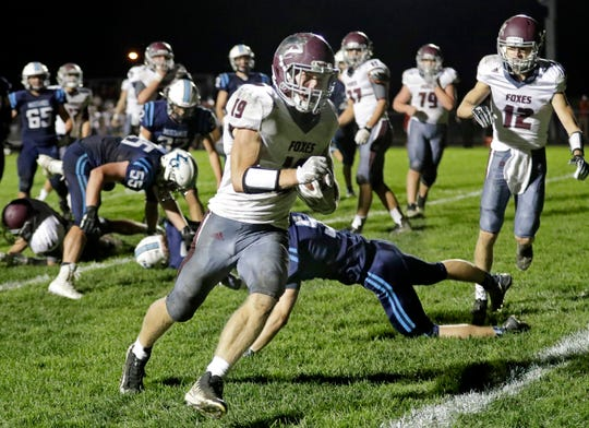 Fox Valley Lutheran's Andrew Behm (19) runs for a touchdown against Little Chute during Friday's game in Little Chute.
