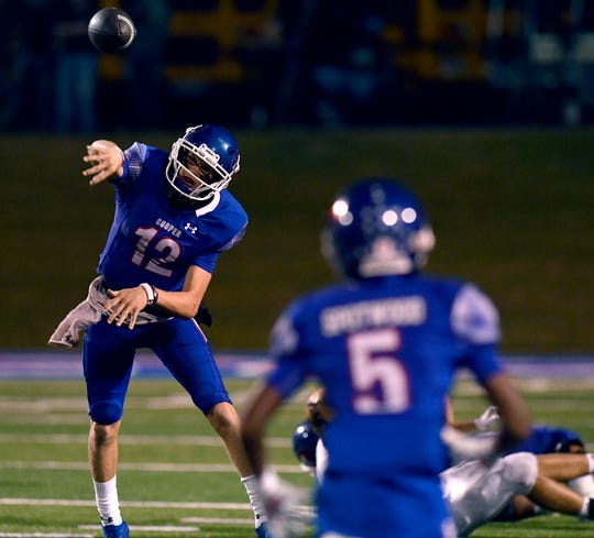 Cooper quarterback Aidan Thompson, left, throws a pass toward Bryan Spotwood (5) during Friday's Crosstown Showdown game against Abilene High on Sept. 13 at Shotwell Stadium. Cooper won the game 23-14.