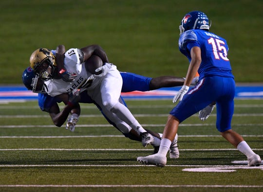 Abilene High's Nathaniel Jones is taken down by Cooper's Ajani Paige during the annual Crosstown Showdown football game Sept. 13 at Shotwell Stadium. Cooper won 23-14.