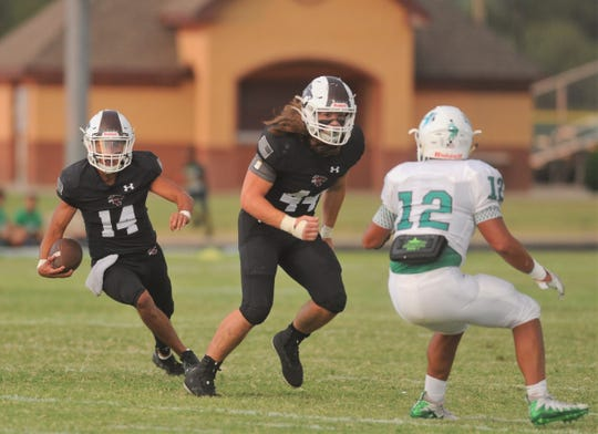 Hawley quarterback Xavier Rodela (14) carries the ball as teammate Colton Marshall looks to block Hamlin's A.J. Ramirez on Friday, Sept. 13, 2019, at Forrest Field in Hawley.