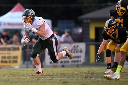 Christ School's Pierce Hammonds runs the ball against Murphy during their game at Murphy High School on Sept. 13, 2019. The Greenies defeated the Bulldogs 27-7.