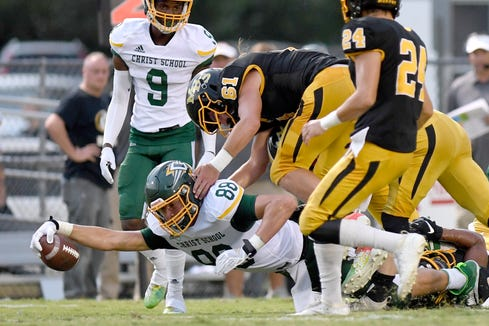 Christ School's Charlie Browder stretches out as Murphy's Parker Posey leaps on top of him during their game at Murphy High School on Sept. 13, 2019. The Greenies defeated the Bulldogs 27-7.