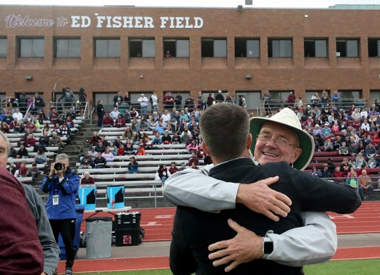 South Kitsap football coach alumni Ed Fisher hugs a family member after the dedication ceremony prior to the  SK vs Rogers football game at the newly named Ed Fisher Field on Friday, September 13, 2019.