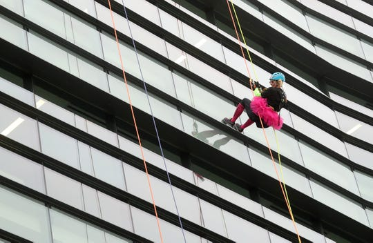 Kate Espy wears a colorful tutu as she makes her way down the side of the Norm Dicks Government Center as part of the Over the Edge fundraiser for Kitsap Strong on Saturday.
