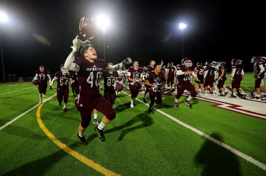 South Kitsap players celebrate on the field after their win over Rogers on Friday, September 13, 2019.