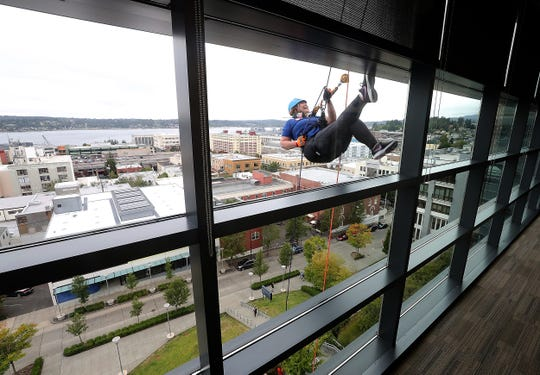 Jill Brenner, of Kitsap Community Resources, smiles as she rappels past the sixth-floor windows of the Norm Dicks Government Center as part of the Over the Edge fundraiser for Kitsap Strong on Saturday.