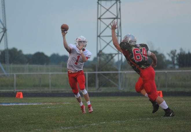 Plymouth's Walker Elliott throws past the on-rushing Tommy Phillips of Buckeye Central.