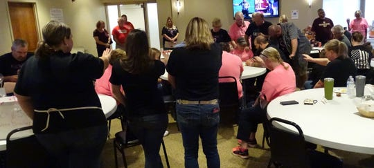 "In an impromptu prayer service, people attending the ""Kickin' it with Kim"" benefit on Saturday pray for the cancer patient."