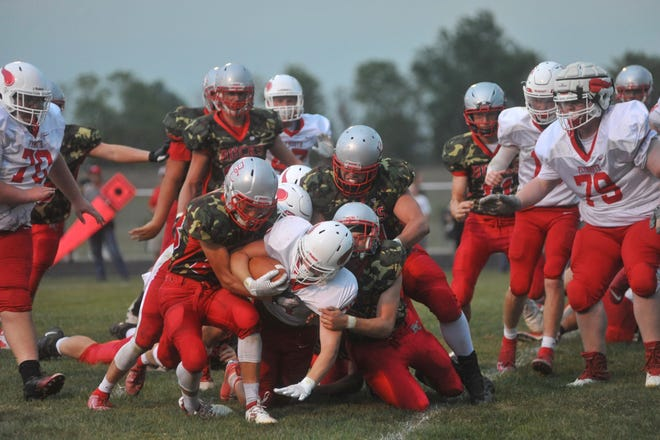 Buckeye Central's defense gang-tackles Plymouth's Lukas Montgomery.