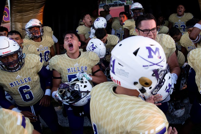 Miller players cheer before running out of their inflatable at the start of their game against Victoria East at Buccaneer Stadium on Friday Sept. 13, 2019.