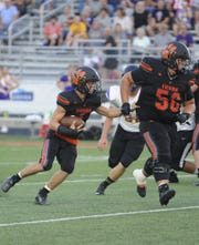 Waverly running back Payton Shoemaker runs behind offensive lineman Andrew Welch during a game against Unioto in Waverly, Ohio on Friday Sept. 13, 2019.