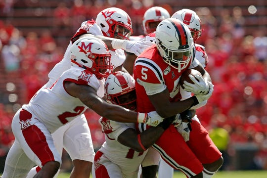 Cincinnati Bearcats running back Tavion Thomas (5) is piled on during a carry in the fourth quarter of the NCAA football game between the Cincinnati Bearcats and the Miami (Oh) Redhawks at Nippert Stadium in Cincinnati on Saturday, Sept. 14, 2019. The Bearcats retained the Victory Bell trophy for the 14th consecutive year with a 35-13 win.