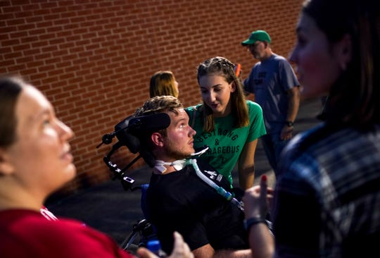 Landry Clardy, Jefferey's girlfriend, leans in from the side of Jeffery Cox's wheelchair as the two share a moment while the game plays on at a TSSAA football game between Houston County and Jo Byrns at Houston County High School in Erin, Tenn., on Friday, Sept. 13, 2019.