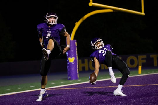Waukee's Xzavier Moore (31) is knocked over by Waukee's Mitch Randall (4) as they celebrate a touchdown during their football game on Friday, Sept. 13, 2019 in Waukee.