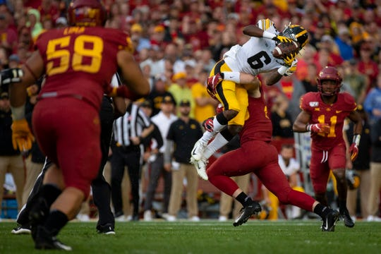 Iowa junior wide receiver Ihmir Smith-Marsette (6) catches a pass as Iowa State linebacker Mike Rose (So.) (23) tackles him during the Cy-Hawk football game at Jack Trice Stadium on Saturday, Sept. 14, 2019 in Ames. A lightning strike forced a delay in the first quarter.