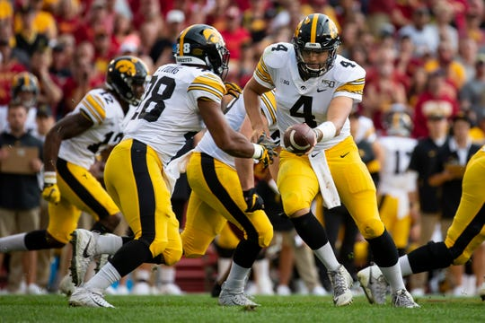 Iowa senior quarterback Nate Stanley (4) hands off to Iowa junior running back Toren Young (28) during the Cy-Hawk football game at Jack Trice Stadium on Saturday, Sept. 14, 2019 in Ames.