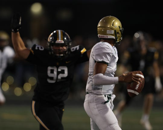 Sept 13, 2019; Pleasant Hill, IA, USA; Southeast Polk Rams Ethan Butcher pressures Iowa City West Trojans QB Marcus Morgan at Southeast Polk High School. The Rams beat the Trojans 23 to 21.  Mandatory Credit: Reese Strickland-For the Herald