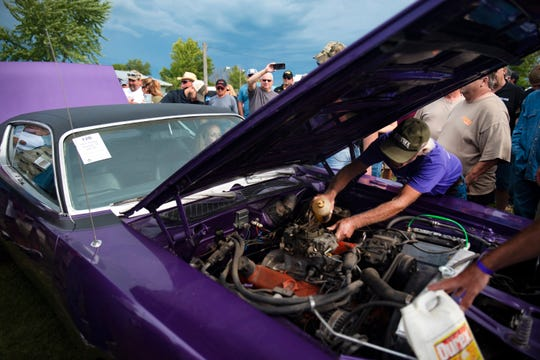 """Bill """"Coyote"""" Johnson helps rear the engines of various cars before auctioning his collection at Vanderbrink Car Auction on Saturday in Red Oak, Iowa. Johnson has collected more than 90 muscle cars since age 16 and kept a select few models following the auction."""