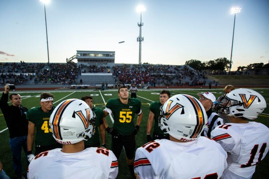 Cedar Rapids Kennedy and West Des Moines Valley captains meet at midfield for the coin toss during a Class 4A varsity football game, Friday, Sept. 13, 2019, at Kingston Stadium in Cedar Rapids, Iowa.