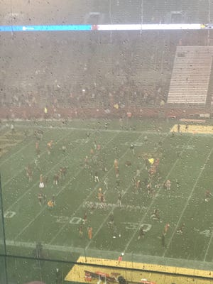 Students rush onto the field at Jack Trice Stadium during the second weather delay on Saturday, Sept. 14.