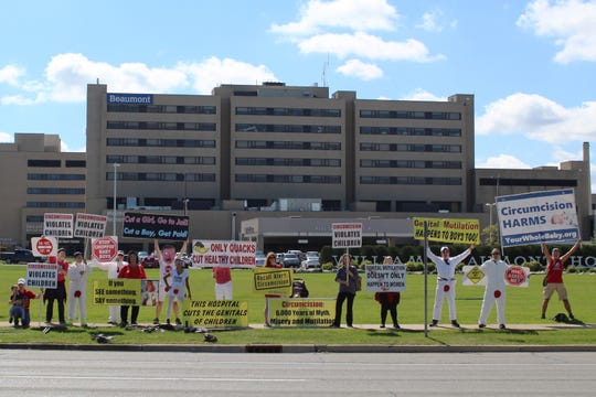 Protesters and members of NOCIRC of Michigan stand in front of Beaumont Hospital in Royal Oak, Saturday, Sept. 14, 2019.