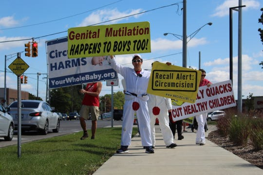 Norm Cohen, founder of NOCIRC, holds signs protesting male circumcision on a march from Memorial Park to Beaumont Hospital in Royal Oak, Saturday, Sept. 14, 2019.