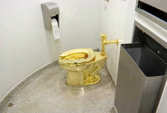 """This Sept. 16, 2016 file image made from a video shows the 18-karat toilet, titled """"America,"""" by Maurizio Cattelan in the restroom of the Solomon R. Guggenheim Museum in New York."""