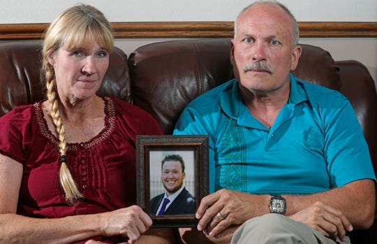Rod and Tonya Meldrum hold a portrait of their son Devin Meldrum, in Provo, Utah. He suffered from debilitating cluster headaches and fatally overdosed after taking a single fentanyl-laced counterfeit oxycodone pill purchased from a dark-web store run by Aaron Shamo, according to his family and authorities.