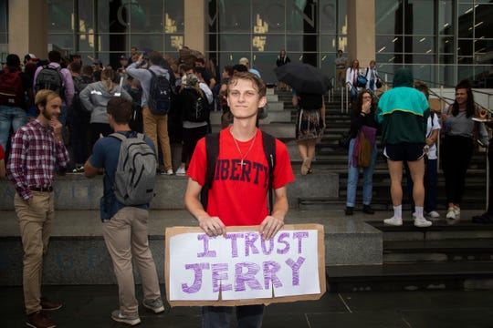 """Garreidy Hamilton, a freshmen in governments and policy, holds a sign reading """"I trust Jerry"""" during a student protest on Friday, Sept. 13, 2019, at Liberty University in Lynchburg, Va. Students at Liberty University gathered to protest in the wake of news articles alleging that school president Jerry Falwell Jr. """"presides over a culture of self-dealing"""" and improperly benefited from the institution."""