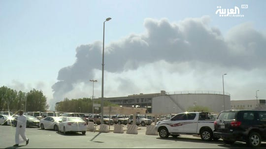 In this image made from a video broadcast on the Saudi-owned Al-Arabiya satellite news channel on Saturday, Sept. 14, 2019, a man walks through a parking lot as the smoke from a fire at the Abqaiq oil processing facility can be seen behind him in Buqyaq, Saudi Arabia.