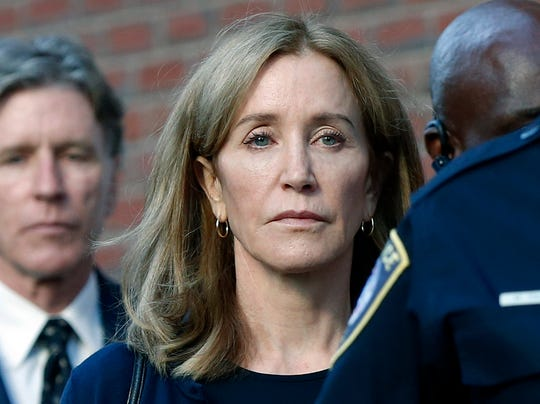 Felicity Huffman leaves federal court with her brother Moore Huffman Jr. following, after she was sentenced in a nationwide college admissions bribery scandal, Friday, Sept. 13, 2019, in Boston.