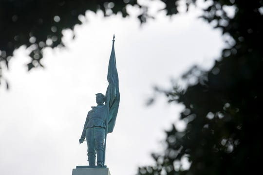 File- This July 19, 2019, file photo shows Norfolk's Confederate monument in the middle of downtown on East Main Street in Norfolk, Va.  Virginia's second largest city is suing the state in an attempt to remove an 80-foot-tall Confederate monument from its downtown. The city of Norfolk's suit was filed Monday, Aug. 19, 2019, in federal court and targets a Virginia law that prevents the removal of war memorials.