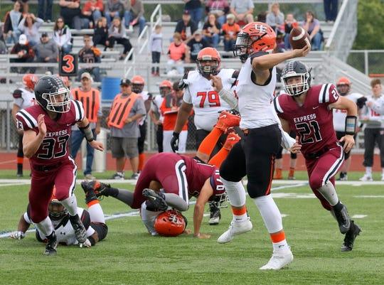 Union-Endicott quarterback Zachary Pilarcek makes a throw against Elmira as Nate Latshaw (21) and Tyler Marks (33) rush the passer Sept. 14, 2019 at Ernie Davis Academy's Marty Harrigan Athletic Field.