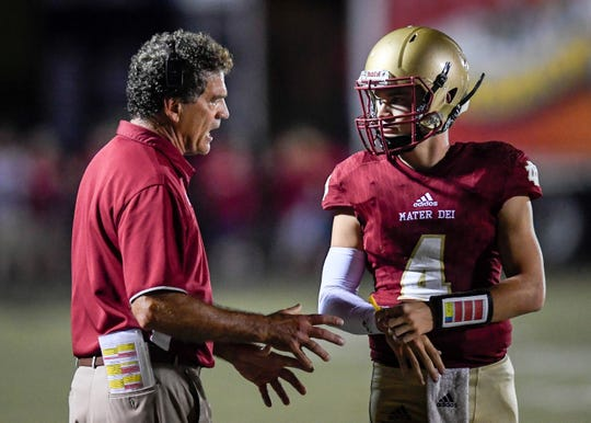Mater Dei head coach Mike Goebel talks with quarterback Cole Happe (4) as the Memorial Tigers play the Mater Dei Wildcats at the Reitz Bowl Friday evening, September 13, 2019.