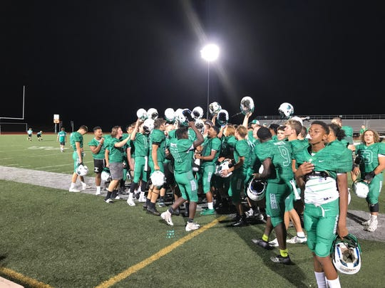 The North football team raises their helmets while singing the school fight song following Friday's 49-6 victory over Harrison.