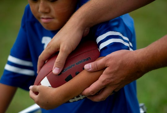 Evansville Junior Football League Colts Coach Justin Haag teaches Andrew Marsh of Evansville, 8, how to hold a football before the Colts vs Broncos game at Howell Park in Evansville, Saturday afternoon, Sept. 14, 2019.