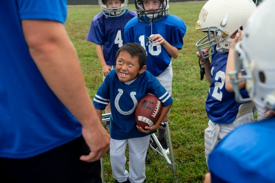 Andrew Marsh of Evansville, 8, smiles up at Colts Coach Justin Haag while warming up before the Evansville Junior Football League Colts vs Broncos game at Howell Park in Evansville, Saturday afternoon, Sept. 14, 2019.
